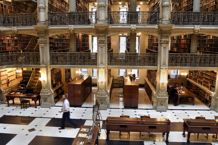 Paul Espinosa, left, curator, walks across the floor at the George Peabody Library.  (Barbara Haddock Taylor/Baltimore Sun)