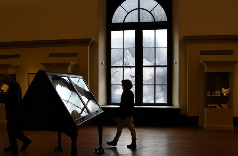 "Visitors walk through an exhibit called ""The Enigmatic Edgar A. Poe In Baltimore and Beyond."" The exhibit contains items from the private collection of Susan Jaffe Tane that are on display at the George Peabody Library until February 5. (Barbara Haddock Taylor/Baltimore Sun)"