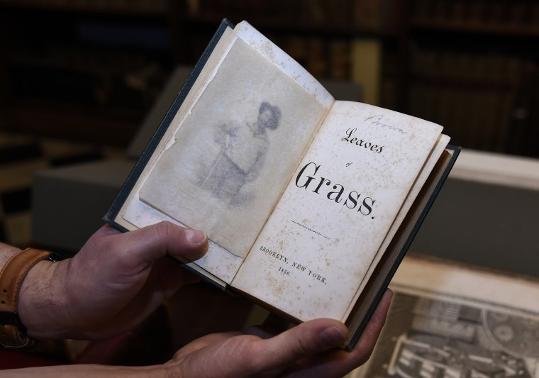"Paul Espinosa, curator, holds an 1856 second edition of ""Leaves of Grass"" by Walt Whitman, one of the many treasures at the Peabody Library.  (Barbara Haddock Taylor/Baltimore Sun)"
