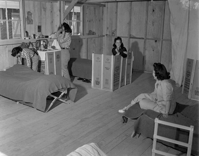 "Three young Japanese women, so-called ""Voluntary Evacuees,"" fro strategic Los Angeles defense areas, are shown as they help prepare the Owens Valley Alien Reception Center at Manzanar, for the many thousands yet to come. Note picture of General Douglas MacArthur hanging on the wall (top left in photo. U642533ACME/CREDIT: BETTMANN-UPI"