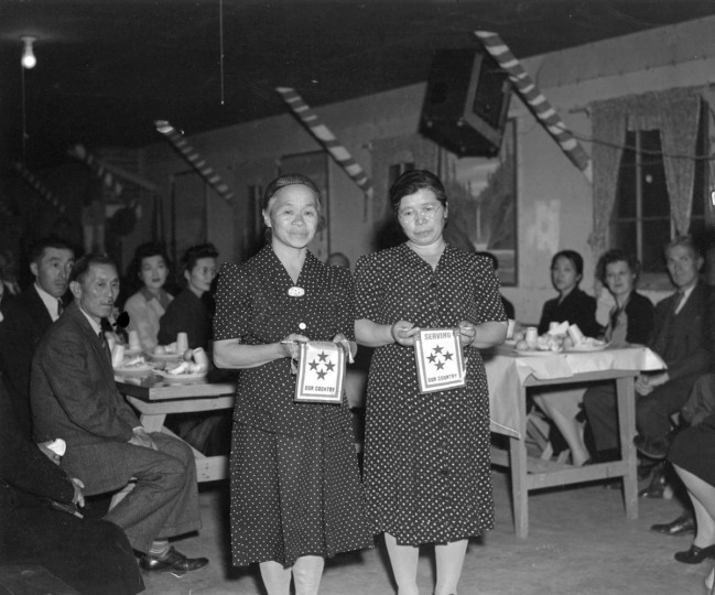 Two women at the Internment Camp in Heart Mountain, Wyoming.  Here, Tsuneishi's mother and Shima Yamaguchi Takata (RT) holds Four-Stars (means that they have four children fighting in the WWII).  They are the only two mothers in Heart Mountain Internment camp having four children serving for the U.S.  This was taken in 1944.  NATIONAL ARCHIVE