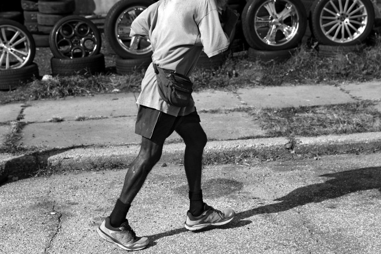 "Keith Boissiere runs past a tire and wheel shop on Belair Road on November 2, 2016. With more than 15 different routes, and at his prime burning through sneakers every two to three months, he held a daily streak of twelve and a half years which helped him earn the nickname of the 'Running Man' by residents. ""I've been through blizzards, ice storms, heat waves, everything just to keep the streak,"" Boissiere said. ""It was all about the streak."" His fascination with ultra running, which is training at distances longer than a marathon, has even on occasion taken him on a more than seven hour journey one way from Baltimore to Washington, DC. Keith Boissiere has been running nearly every day for the past three decades - averaging more than 20 miles per day - for his health. Many residents only know the enigmatic figure by his nickname of the 'Running Man.' (Patrick Smith/Getty Images)"