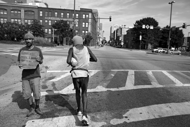 Keith Boissiere (r) runs past a man holding a sign that reads 'Homeless...Type 1 Diabetes... Anything Helps...God Bless!!' on Martin Luther King Boulevard on September 15, 2016. According to data provided by The City of Baltimore and the Mayor's Office of Human Services, there are an estimated  2,800 homeless in Baltimore. Though only a rumor, the 'Running Man' is not homeless, but does collect government assistance in the form of: Supplemental Security Income, the Food Supplement Program, and Medicaid. He was deemed unfit to work because of his serious health conditions, which include problems with his heart and kidneys. Keith Boissiere has been running nearly every day for the past three decades - averaging more than 20 miles per day - for his health. Many residents only know the enigmatic figure by his nickname of the 'Running Man' - but Boissiere, 64, is a green-card-carrying Trinidad and Tobago native living in Baltimore. Having never competed, nor having a desire to do so, the 'Running Man' held a daily streak of 12 and a half years which helped him earn his alias. But his health took a turn for the worse in 2008 - the streak ended - as his life almost did, too. (Patrick Smith/Getty Images)