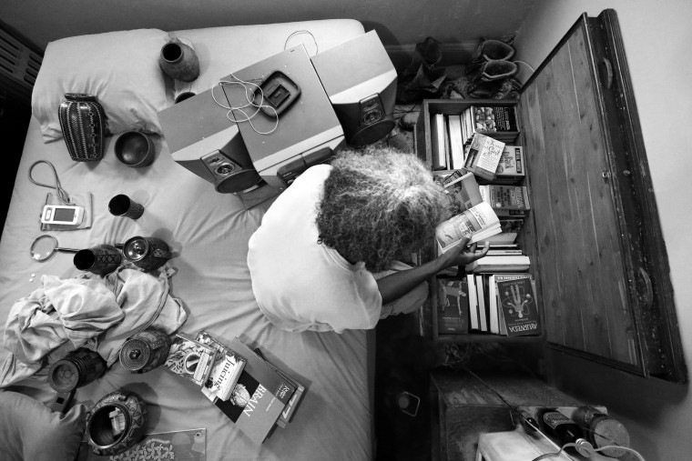 "Keith Boissiere turns the pages of a book as he searches through a trunk of literature in his apartment on October 26, 2016. The 'Running Man' lives a simple life in solitude. His routine is regimented as he doesn't own a car, doesn't do drugs, drinks alcohol only on rare occasion, isn't religious, and doesn't have a computer, nor smart phone. Other than running, which takes him four hours daily, the Howard University mechanical engineering graduate regularly reads in his studio apartment, which is lined with multiple trunks that stockpiles what he estimates is thousands of books on every topic. He says one should not concentrate only on physical fitness while neglecting the brain. What is important is, ""Fitness of the body, fitness of the mind, and understanding and learning what the whole world is about,"" Boissiere said. Keith Boissiere has been running nearly every day for the past three decades - averaging more than 20 miles per day - for his health. (Patrick Smith/Getty Images)"