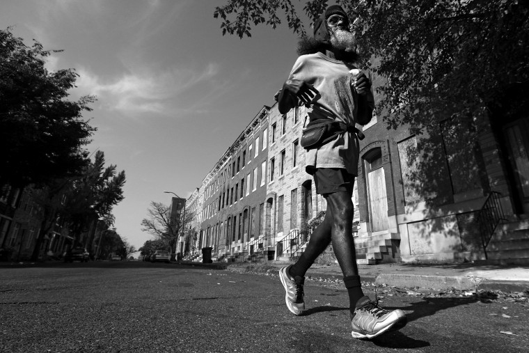 Keith Boissiere runs on Harlem Avenue on November 2, 2016. After being attacked in November 2014, and to help avoid those types of circumstances, Boissiere says that's the reason he only navigates the city in broad daylight. The aging 'Running Man' is still accumulating the miles almost daily. While he no longer has a daily streak because of his ailing health, he takes to the streets whenever he is able. But his health took a turn for the worse in 2008 - the streak ended - as his life almost did, too. Through all of his troubles, which includes being on a kidney donor recipient list, Boissiere copes the only way he knows how - he continues to run - as the hospital encouraged him to do in order to aid his failing health. He doesn't brag about his accomplishments or mention his celebrity-like status despite being constantly acknowledged - and these days barriers such as rain, snow and hospital appointments often dictate his running schedule. His drive and passion for his own health is often described as bringing positivity and strength to residents in the city, and the people of Baltimore still witness the 'Running Man' from West to East, and North to South, as he competes with only himself to stay upright by staying fit in a city plagued by: drugs, guns, crime, and violence. (Patrick Smith/Getty Images)