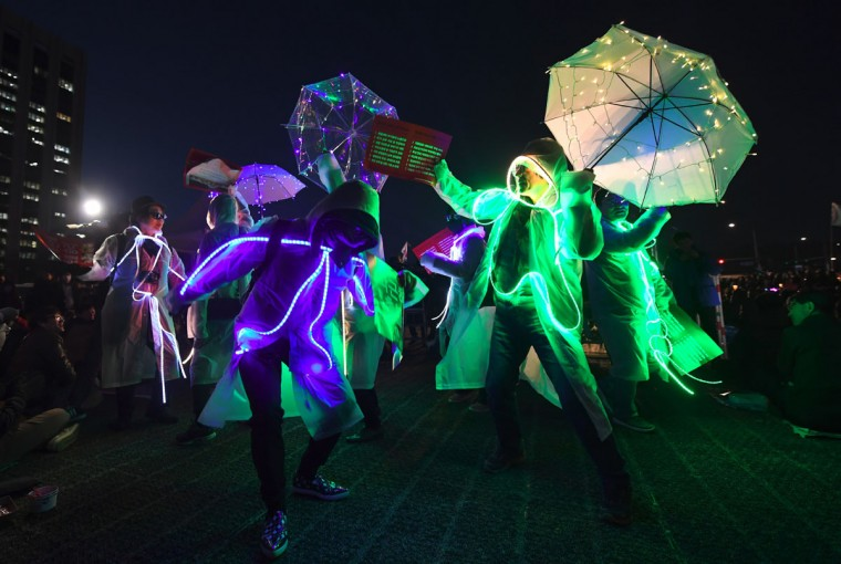 South Korean demonstrators wearing illuminated costumes take part in a candlelit rally demanding arrest of the impeached-president Park Geun-Hye in Seoul on March 10, 2017 after the announcement of the Constitutional Court's decision to uphold the impeachment of South Korea's President Park Geun-Hye.South Korean President Park Geun-Hye was fired on March 10 as a court upheld her impeachment over a corruption scandal that has paralysed the nation at a time of mounting tensions in East Asia. / (AFP Photo/Jung (photo credit should read jung yeon-je)