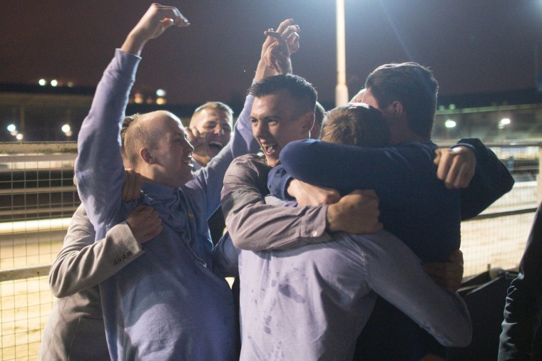 Racegoers celebrate winning a bet during an evening of greyhound racing at the Wimbledon Stadium dog track in south London on March 18, 2017. March 25 will see the final day of racing at the Wimbledon dog track which will close to be demolished to make way for a new stadium for AFC Wimbledon. The closer of track will mark the end of the once hugely popular working-class sport of greyhound racing in London. (Justin Tallis/AFP/Getty Images)