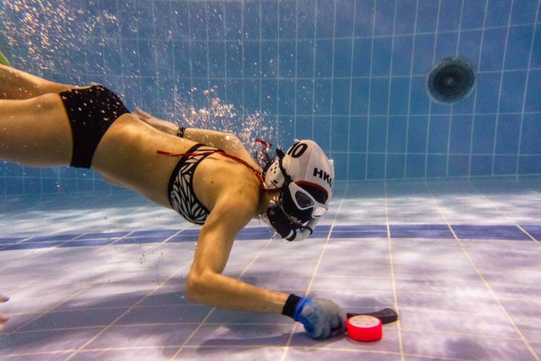 "In this photo taken on February 15, 2017, a member of the ""HK Typhoon"" underwater hockey ""dribbles"" the puck during the team's once-a-week team practice session at a 25-meter school pool in Hong Kong. The gravity defying sport of underwater hockey has gained a worldwide following -- now a Hong Kong team is diving in as the game takes off in Asia. (ANTHONY WALLACE/AFP/Getty Images)"