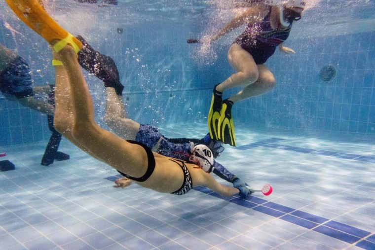 "In this photo taken on February 15, 2017, members of the ""HK Typhoon"" underwater hockey club fight for possession of the puck (bottom right) during their once-a-week team practice session at a 25-meter school pool in Hong Kong. The gravity defying sport of underwater hockey has gained a worldwide following -- now a Hong Kong team is diving in as the game takes off in Asia. (ANTHONY WALLACE/AFP/Getty Images)"