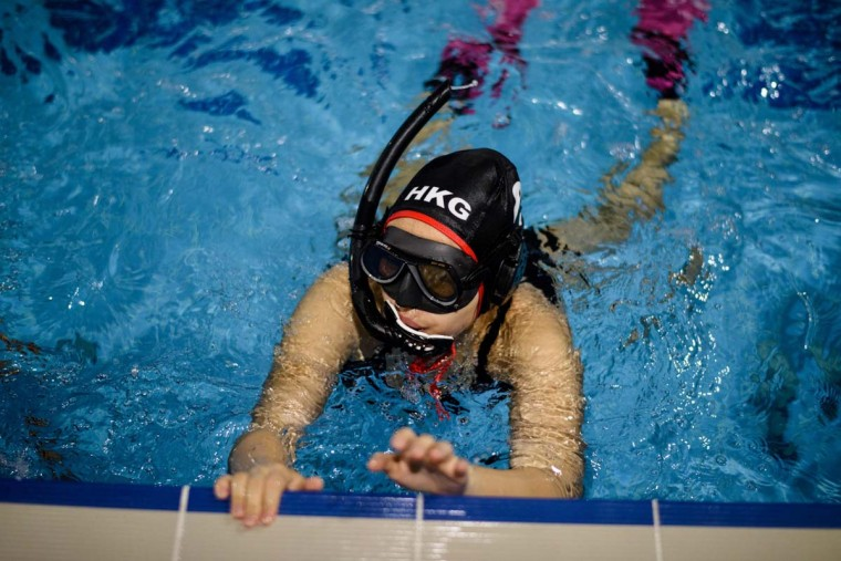 "In this photo taken on February 15, 2017, a member of the ""HK Typhoon"" underwater hockey club completes a lap as she takes part in exercise drills during the team's once-a-week practice session at a 25-meter school pool in Hong Kong. The gravity defying sport of underwater hockey has gained a worldwide following -- now a Hong Kong team is diving in as the game takes off in Asia. (ANTHONY WALLACE/AFP/Getty Images)"