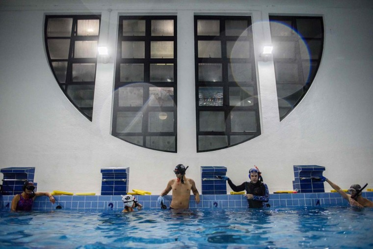 "In this photo taken on February 15, 2017, geologist and former competitive swimmer Henry Chan (center), 28, who founded the ""HK Typhoon"" underwater hockey club, rests with his teammates during their once-a-week team practice session at a 25-meter school pool in Hong Kong. The gravity defying sport of underwater hockey has gained a worldwide following -- now a Hong Kong team is diving in as the game takes off in Asia. (ANTHONY WALLACE/AFP/Getty Images)"