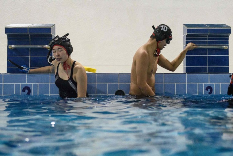 "In this photo taken on February 15, 2017, geologist and former competitive swimmer Henry Chan (right), 28, who founded the ""HK Typhoon"" underwater hockey club, regains his breath with a teammate during their once-a-week team practice session at a 25-meter school pool in Hong Kong. The gravity defying sport of underwater hockey has gained a worldwide following -- now a Hong Kong team is diving in as the game takes off in Asia. (ANTHONY WALLACE/AFP/Getty Images)"