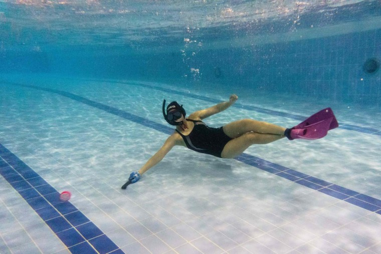 "In this photo taken on February 15, 2017, a member of the ""HK Typhoon"" underwater hockey club reaches for the puck during the team's once-a-week practice session at a 25-meter school pool in Hong Kong. The gravity defying sport of underwater hockey has gained a worldwide following -- now a Hong Kong team is diving in as the game takes off in Asia. (ANTHONY WALLACE/AFP/Getty Images)"
