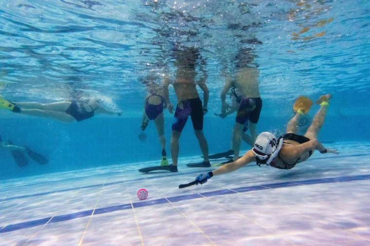 "In this photo taken on February 15, 2017, a member (right) of the ""HK Typhoon"" underwater hockey reaches for the puck during their once-a-week team practice session at a 25-meter school pool in Hong Kong. The gravity defying sport of underwater hockey has gained a worldwide following -- now a Hong Kong team is diving in as the game takes off in Asia. (ANTHONY WALLACE/AFP/Getty Images)"