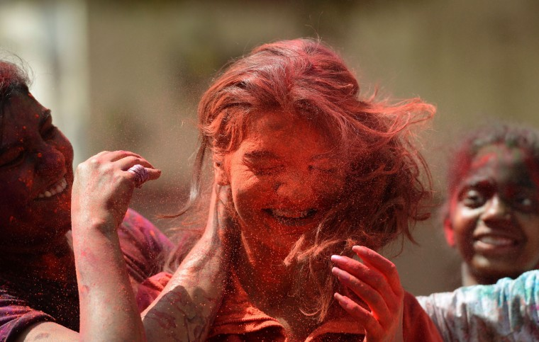 An Indian woman is smeared with coloured powder during the Holi celebrations in Mumbai on March 13, 2017. Holi, the festival of colours, is a riotous celebration of the coming of spring and falls on the day after full moon annually in March. (Punit Paranjpe/AFP/Getty Images)