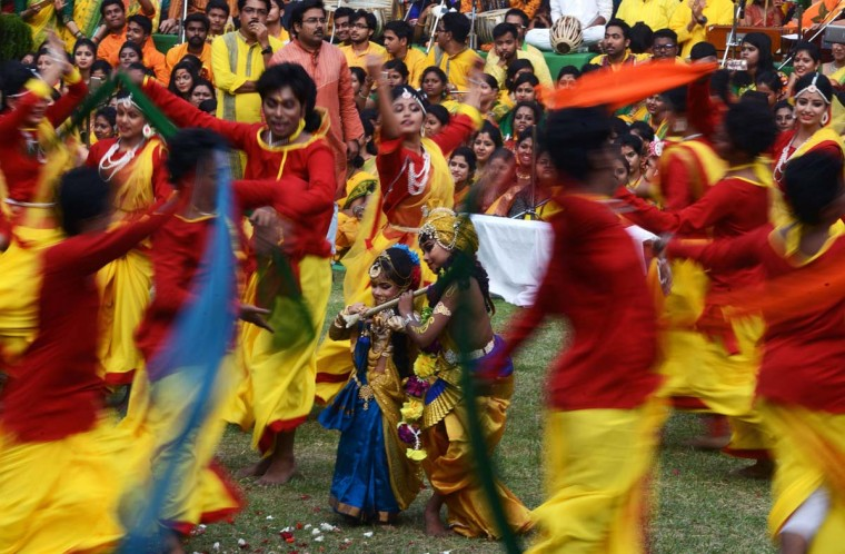 Indian children walk among dancing students at an event to celebrate the Hindu festival of Holi in Kolkata on March 7, 2017. Holi, the popular Hindu spring festival of colors is observed in India at the end of the winter season on the last full moon of the lunar month, and will be celebrated on March 13 this year. (DIBYANGSHU SARKAR/AFP/Getty Images)