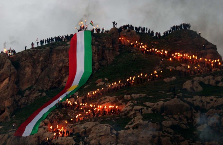 Iraqi Kurds holding lit torches walk up a mountain, draped in a large Kurdish flag, in the town of Akra, 500 km north of Baghdad, on March 20, 2017 as they celebrate the Noruz spring festival. (SAFIN HAMED/AFP/Getty Images)