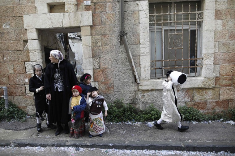 An ultra-Orthodox Jewish family wearing costumes walk in the street in Jerusalem's Mea Shearim ultra-Orthodox neighbourhood on March 13, 2017 during the religious holiday of Purim. The carnival-like Purim holiday is celebrated with parades and costume parties to commemorate the deliverance of the Jewish people from a plot to exterminate them in the ancient Persian Empire 2,500 years ago, as recorded in the Biblical Book of Esther. (AFP PHOTO / MENAHEM KAHANA)