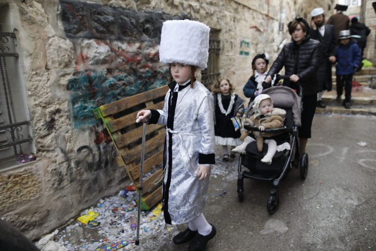 Ultra-Orthodox Jewish children wearing costumes walk in Jerusalem's Mea Shearim ultra-Orthodox neighbourhood on March 13, 2017 during the religious holiday of Purim. The carnival-like Purim holiday is celebrated with parades and costume parties to commemorate the deliverance of the Jewish people from a plot to exterminate them in the ancient Persian Empire 2,500 years ago, as recorded in the Biblical Book of Esther. (AFP PHOTO / MENAHEM KAHANA)
