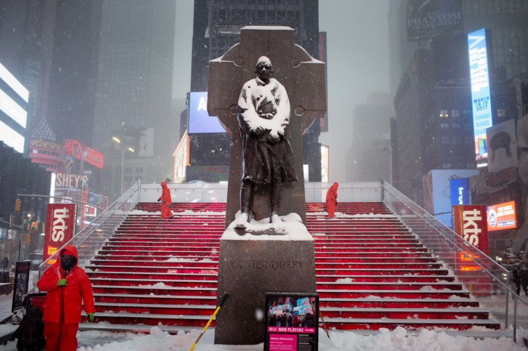 Times Square Alliance workers maintain the red steps in Father Duffy Square during a day of heavy snow and freezing rain on March 14, 2017 in New York City. Much of the Northeast is under a state of emergency as a blizzard is expected to bring over one foot of snow and high winds to the area. (Photo by Kevin Hagen/Getty Images)