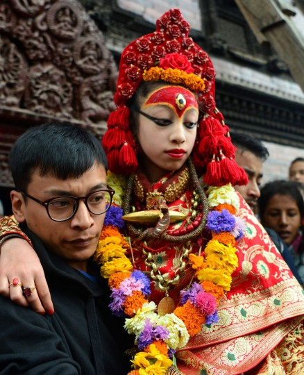 A Nepalese priest carries the Living Goddess, the Kumari, during the Ghode Jatra (Horse Race) Festival in Kathmandu on March 27, 2017. The Kumari is worshipped by both Hindus and Buddhists as a living goddess and a protector bringing good luck and prosperity. (Prakash Mathema/AFP/Getty Images)