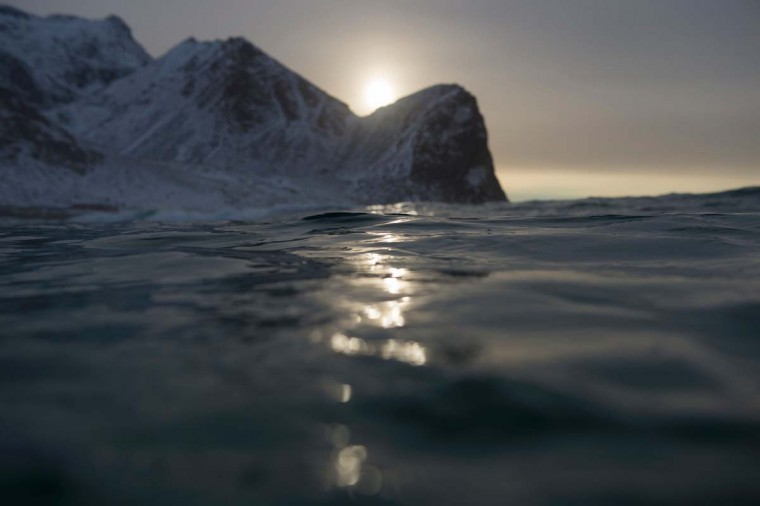 Snow-covered mountains are seen from the waters of Unstad along the northern Atlantic Ocean on March 12, 2017. (OLIVIER MORIN/AFP/Getty Images)