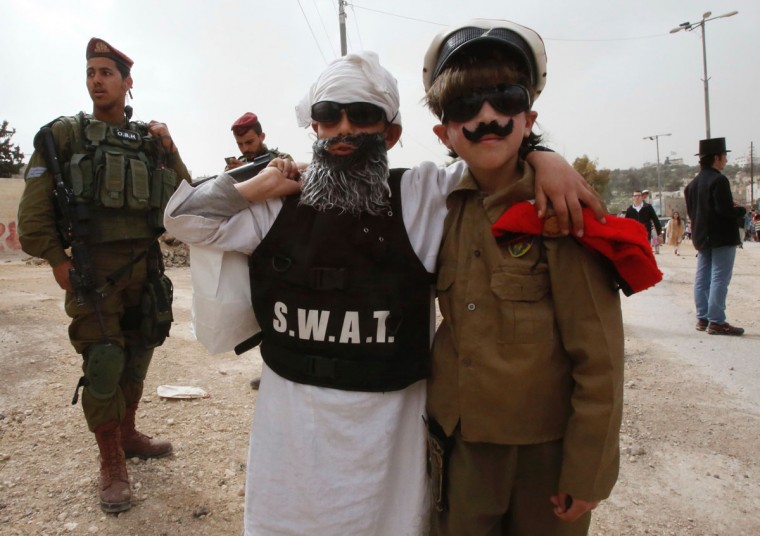 Young Israeli settlers wearing costumes pose for a picture during a parade to celebrate the Jewish holiday of Purim in al-Shuhada Street, in the West Bank town of Hebron, on March 12, 2017. The carnival-like Purim holiday is celebrated with parades and costume parties to commemorate the deliverance of the Jewish people from a plot to exterminate them in the ancient Persian Empire 2,500 years ago, as recorded in the Biblical Book of Esther. (AFP PHOTO / HAZEM BADER)