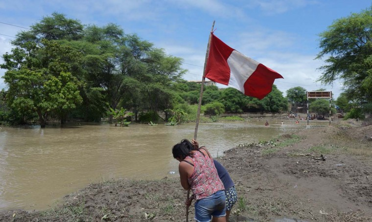 Women raise a national flag next to rising waters in Piura, northern Peru on March 28, 2017. (MIGUEL ARREATEGUI/AFP/Getty Images)