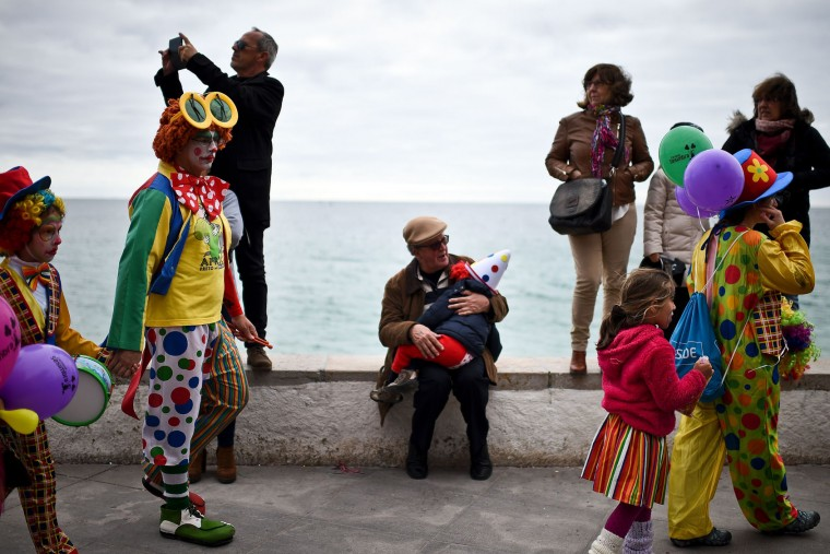 A man holds a child dressed as a clown during the Carnival Clown's Parade at Sesimbra village on February 27, 2017. (Patricia de Melo Moreira/AFP/Getty Images)