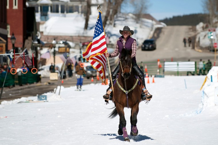 Flag bearer Jesslyn Swirka rides her horse down Harrison Avenue in Leadville, Colorado at the start of the 68th annual Leadville Ski Joring weekend competition on Saturday, March 4, 2017 in Leadville, Colorado. Skijoring, which has its origins as a competitive sport in Scandinavia, has been adapted over the years to include a team made up of a rider and skier who must navigate jumps, slalom gates, and the spearing of rings for points. Leadville, with an elevation of 10,152 feet (3,094 m), the highest incorporated city in North America, has been hosting skijoring competitions since 1949. (Jason Connolly/AFP/Getty Images)