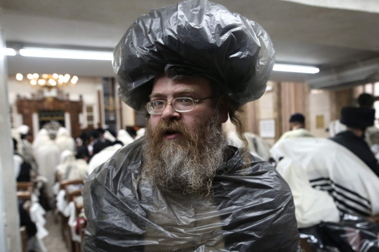 An ultra-Orthodox Jewish man wearing plastic above his clothes and hat is seen at a synagogue as worshippers read the book of Esther in Jerusalem's Mea Shearim ultra-Orthodox neighbourhood on March 13, 2017 during the religious holiday of Purim. The carnival-like Purim holiday is celebrated with parades and costume parties to commemorate the deliverance of the Jewish people from a plot to exterminate them in the ancient Persian Empire 2,500 years ago, as recorded in the Biblical Book of Esther. (AFP PHOTO / MENAHEM KAHANA)