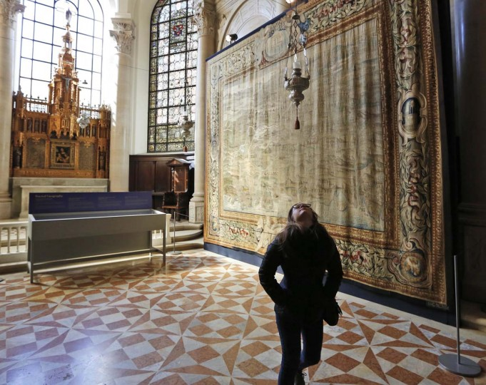 """A woman looks up while browsing an exhibit of tapestries at the Cathedral of St. John the Divine in New York, Wednesday, March 22, 2017. Experts at the cathedral just spent 16 years sprucing up its super-size wall hangings with a labor-intensive process that uses dental probes, tweezers and other tools. Now the historic house of worship is inviting the public to enjoy the fruits of its labors. An exhibit called """"The Barberini Tapestries, Scenes from the Life of Christ"""" runs through June 25. (AP Photo/Seth Wenig)"""