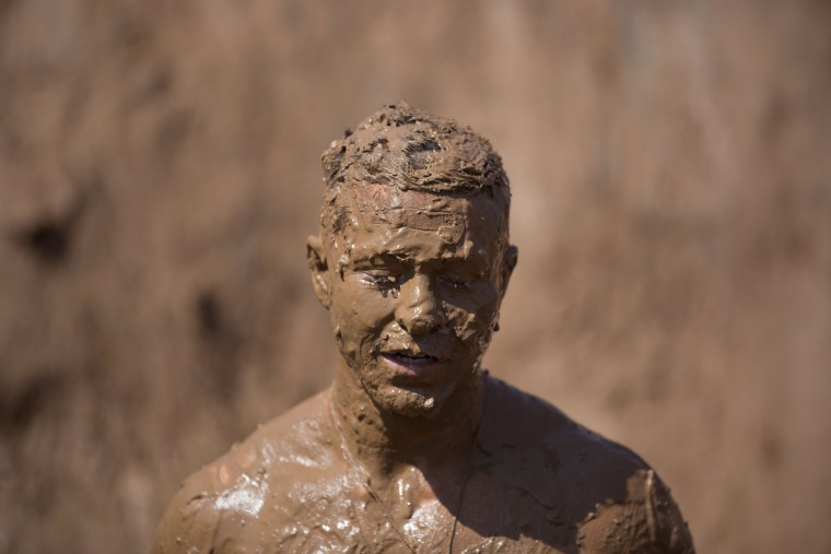 A participant takes part in the Mud Day race, a 13km obstacle course in Tel Aviv, Israel, Friday, March 24, 2017. (AP Photo/Oded Balilty)