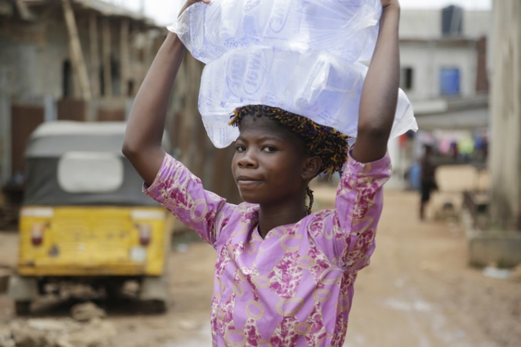 A woman carries bags of sachet water she bought on a street in Baruwa Lagos, Nigeria Wednesday, March 22, 2017. (Sunday Alamba/AP)
