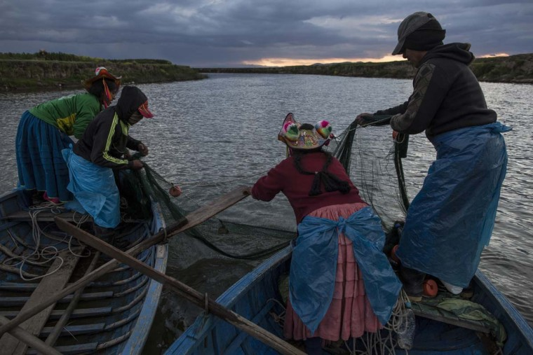 In this Feb. 3, 2017 photo, the Avila family fishes on the Coata River, which flows into Lake Titicaca, in the Puno region of Peru. Untreated sewage water drains from two dozen nearby cities, and illegal gold mines high in the Andes dump up to 15 tons of mercury a year into the river leading to the lake. (AP Photo/Rodrigo Abd)