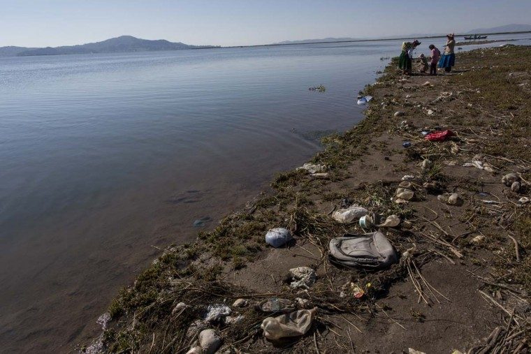 "In this Feb. 3, 2017 photo, trash covers the shores of Lake Titicaca where environmental activist Maruja Inquilla talks to locals in Coata, in the Puno region of Peru. Inquillla is alerting neighboring villagers of the dangers lurking in their food and water. ""the frogs could talk they would say, ""This is killing me,"" she said. (AP Photo/Rodrigo Abd)"