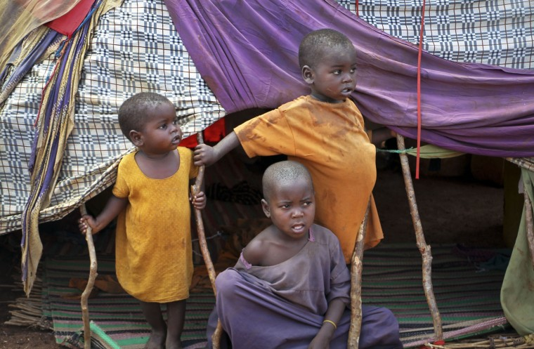 In this photo taken Saturday, March 25, 2017, newly displaced Somali children stand outside their makeshift shelter at a camp in Baidoa, Somalia. Somalia's drought is threatening 3 million lives according to the U.N. and in recent months aid agencies have been scaling up their efforts but say more support is urgently needed to prevent the crisis from worsening. (AP Photo/Farah Abdi Warsameh)