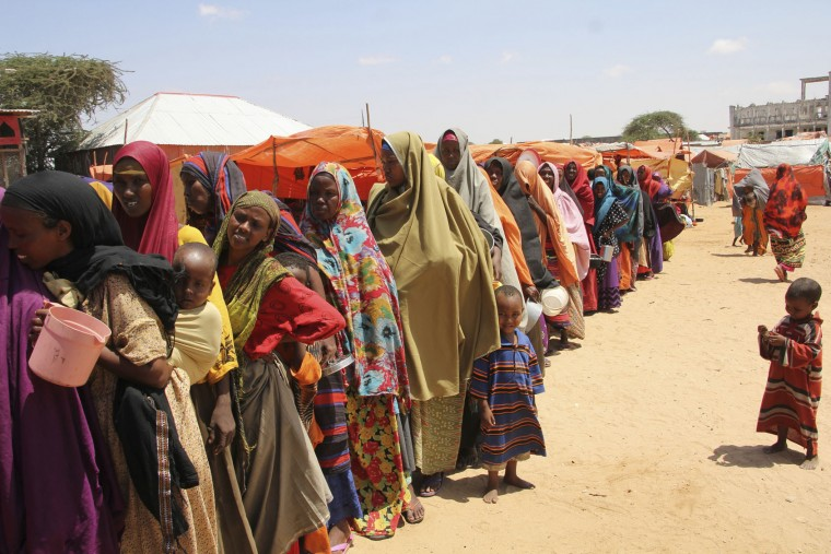 Displaced Somali women stand in queue to receive food handouts in a camp outside of Mogadishu, Somalia, Monday, March, 27, 2017. Somalia's drought is threatening 3 million lives according to the U.N. and in recent months aid agencies have been scaling up their efforts but say more support is urgently needed to prevent the crisis from worsening. (AP Photo/Farah Abdi Warsameh)