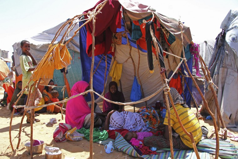 Newly displaced Somali women and children sit in a makeshift shelter in camp just outside of Mogadishu, in Somalia, Monday, March, 27, 2017. Somalia's drought is threatening 3 million lives, according to the U.N. In recent months, aid agencies have been scaling up their efforts but they say said more support is urgently needed to prevent the crisis from worsening. (AP Photo/Farah Abdi Warsameh)
