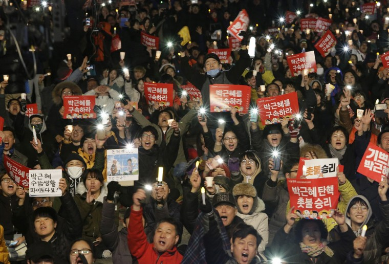 "Protesters shout slogans during a rally calling for impeached President Park Geun-hye's arrest in Seoul, South Korea, Friday, March 10, 2017. The Constitutional Court removed impeached President Park Geun-hye from office in a unanimous ruling Friday over a corruption scandal that has plunged the country into political turmoil and worsened an already-serious national divide. The signs read ""Park Geun-hye's arrest."" (AP Photo/Ahn Young-joon)"