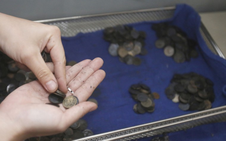 "Coins removed from the female green turtle nicknamed ""Bank"" are counted after her surgery at Chulalongkorn University's veterinary faculty in Bangkok, Thailand, Monday, March 6, 2017. Veterinarians operated Monday on ""Bank,"" removing less than 1,000 coins from the endangered animal. Her indigestible diet was a result of many tourists seeking good fortune tossing coins into her pool over many years in the eastern town of Sri Racha. (AP Photo/Sakchai Lalit)"