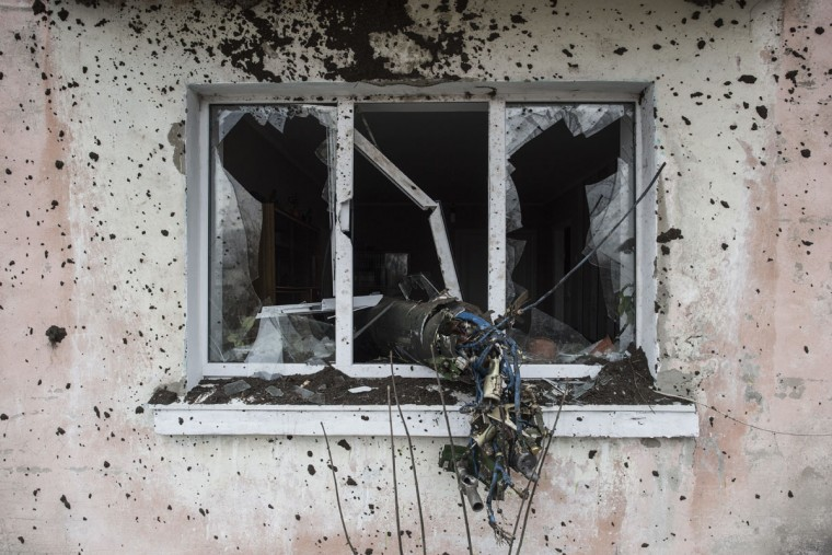 An apartment house is damaged by a missile after a massive fire at a military depot in Balaklia, Ukraine, Friday, March 24, 2017. About 20,000 people were evacuated in Kharkiv region near the border with Russia when the fire broke out Thursday at one of Ukraine's largest military arsenals, which held huge stocks of large-caliber artillery rounds. (AP Photo/Evgeniy Maloletka)