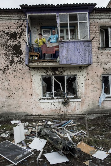 Residents stand on the balcony of an apartment house damaged by a missile after a massive fire at a military depot in Balaklia, Ukraine, Friday, March 24, 2017. About 20,000 people were evacuated in Kharkiv region near the border with Russia when the fire broke out Thursday at one of Ukraine's largest military arsenals, which held huge stocks of large-caliber artillery rounds. (AP Photo/Evgeniy Maloletka)
