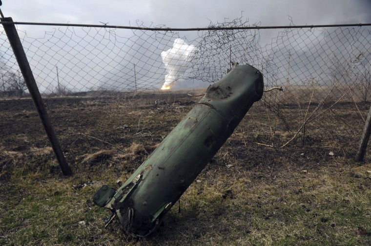 A part of a missile seen is on the ground, as fire rages at a military ammunition depot in the background, in Balaklia, Ukraine on Thursday, March 23 2017. Around 20,000 people were evacuated Thursday in Ukraine's Kharkiv region near the border with Russia after a massive fire at a military arsenal. The fire at the depot in Balaklia, which holds large-caliber artillery rounds and is one of Ukraine's largest, erupted early Thursday, prompting the evacuation and Prime Minister Volodymyr Groysman to fly to the area to monitor the blaze, which is still raging. An area the size of 40 kilometers (25 miles) around the depot has been closed for flights.(AP Photo/Mykhailo Andriiv)