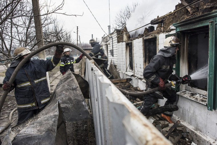 Firefighters extinguish fire in a house which was hit by a shell after a massive fire at a military depot in Balaklia, Ukraine, Friday, March 24, 2017. About 20,000 people were evacuated in Kharkiv region near the border with Russia when the fire broke out Thursday at one of Ukraine's largest military arsenals, which held huge stocks of large-caliber artillery rounds. (AP Photo/Evgeniy Maloletka)
