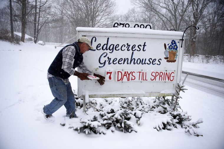 Paul Hammer of Ledgecrest Greenhouses changes the numbers off days remaining until spring on a sign in front of his nursery in Mansfield, Conn., Tuesday, March 14, 2017. A storm pounded the Northeast with more than a foot of snow in places Tuesday, paralyzing much of the Washington-to-Boston corridor after a remarkably mild February had lulled people into thinking the worst of winter was over. (Mark Mirko/Hartford Courant via AP)