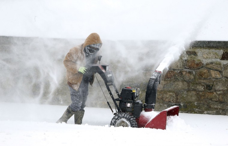Alex Martinez of Morristown, N.J., fights heavy winds as he snow blow on Washington Street in Morristown, N.J., as a Nor'easter blasts N.J. and the Northeast with heavy snow, high winds. The late-winter storm is expected to drop as much as two feet of snow on Morris County, N.J., Tuesday, March 14, 2017. (Bob Karp /The Daily Record via AP)