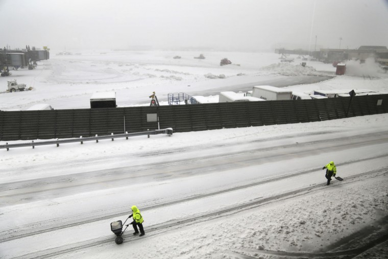 People carry a salt spreader and a shovel at Newark Liberty International Airport in Newark, N.J., Tuesday, March 14, 2017. A storm pounded the Northeast with more than a foot of snow in places Tuesday, paralyzing much of the Washington-to-Boston corridor after a remarkably mild February had lulled people into thinking the worst of winter was over. (AP Photo/Seth Wenig)