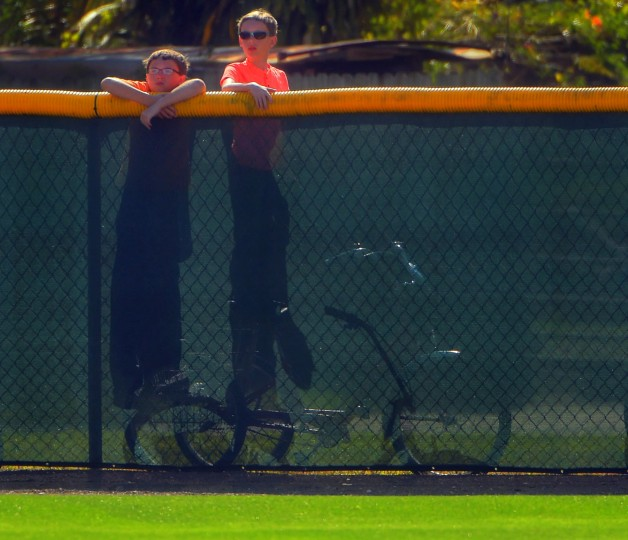 Two children use bikes to elevate themselves above the outfield wall to watch the Baltimore Orioles participate in spring training at the Ed Smith Stadium baseball complex. (Karl Merton Ferron / Baltimore Sun)