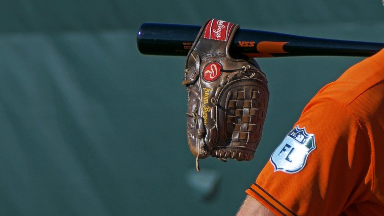 A glove is slung on a fungo bat held by Baltimore Orioles staff during spring training at the Ed Smith Stadium baseball complex. (Karl Merton Ferron / Baltimore Sun)